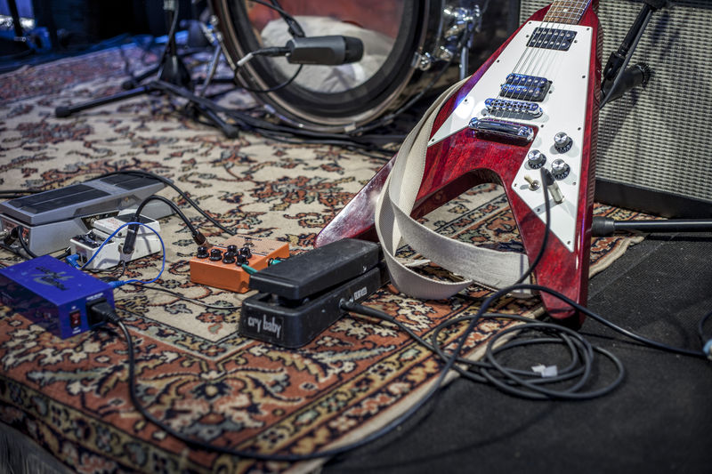 Electric guitar and drum by cables on stage