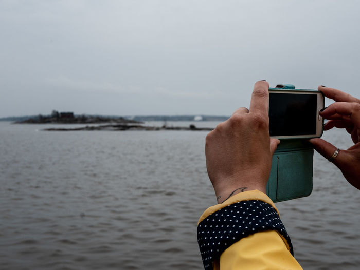Cropped hands of woman photographing sea with smart phone against sky
