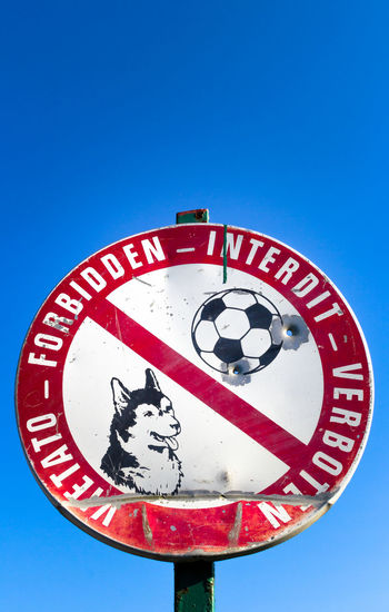 Sign prohibiting access to the dogs and to play football. They are well see two bullet holes. Background Ball Banned Bright Bullet Circle Dent Dented Dog Excluded Football Forbidden Holes Information Law Multilanguage No Park Playground Prohibited Prohibition Public Respect Streetsign Vandalism