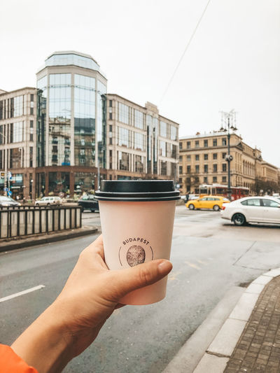 Budapest coffee break City Architecture Human Hand Holding Hand Disposable Drink Real People Cup Street Disposable Cup Day Food And Drink Personal Perspective Focus On Foreground Body Part Outdoors Finger Budapest Hungary