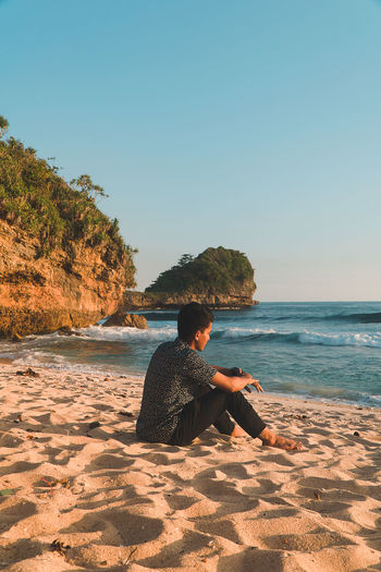 Man sitting on beach looking at sea against clear sky