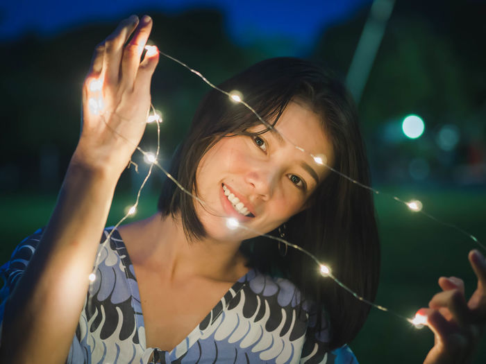 Young woman holding illuminated string lights while sitting on grassy field