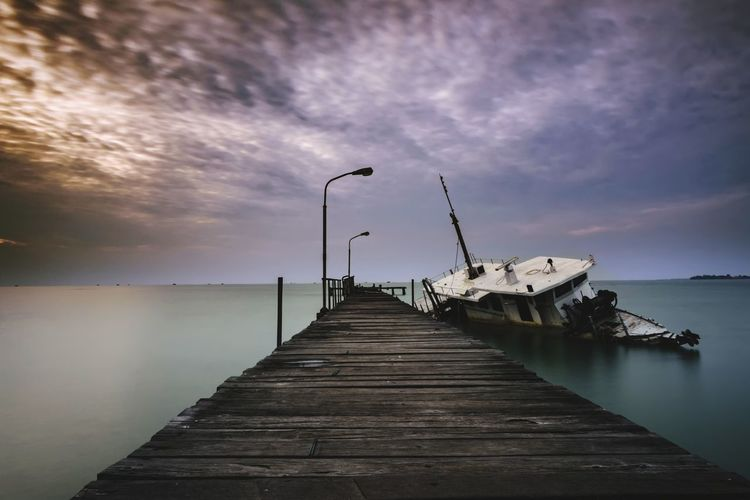 Pier by abandoned boat in sea against cloudy sky during sunset