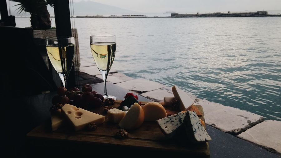 Close-up of fresh food and white wine by sea