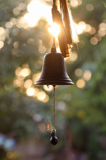 Close-up of bell against trees during sunset