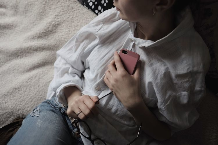 Midsection of woman holding pink mobile phone resting on bed at home