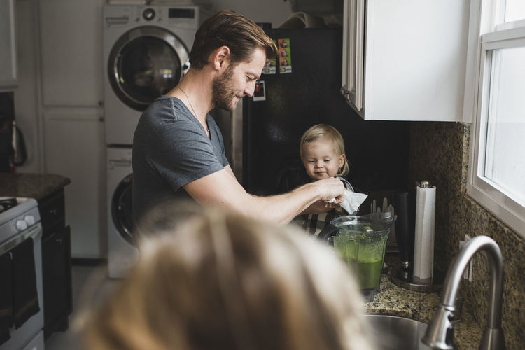 Mid adult man cooking food while daughter sitting on kitchen counter at home