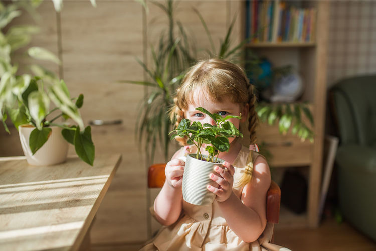 Cute girl holding plant at home