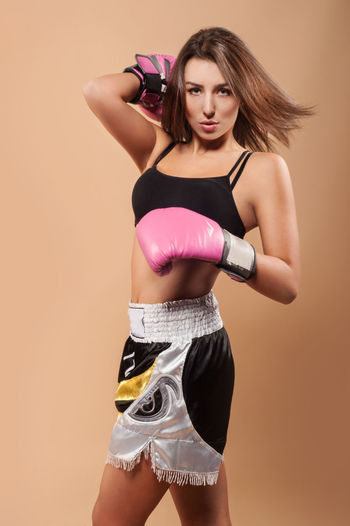 Portrait Of Young Woman With Boxing Gloves Over Beige Background