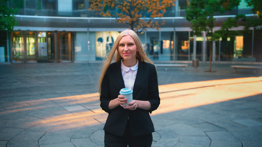 Portrait of young woman standing on footpath holding coffee cup