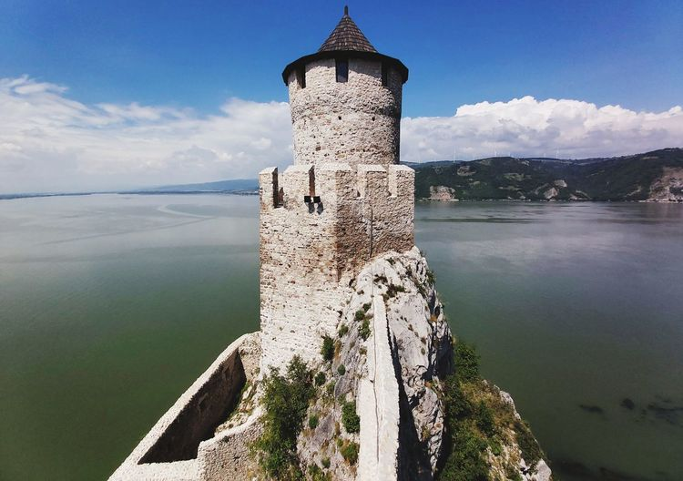 Castle by river against sky