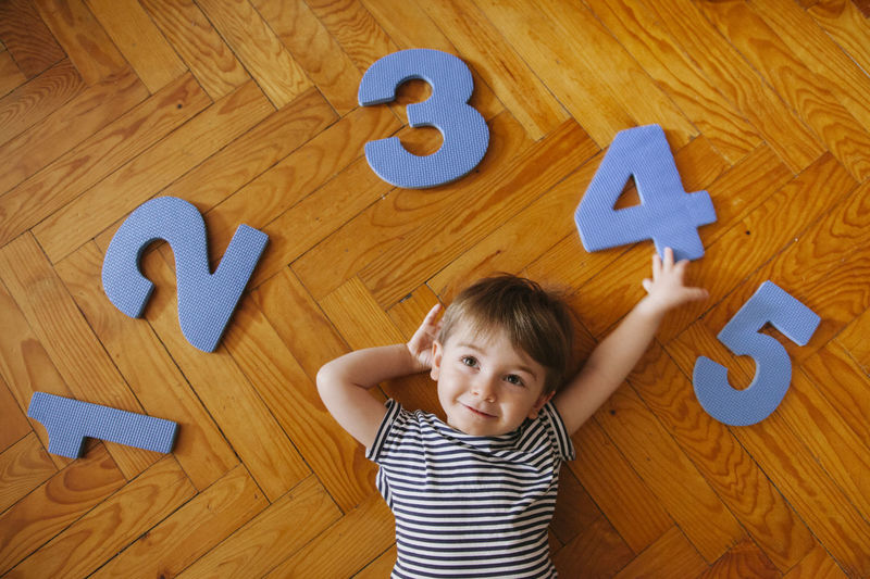 High angle view of cute boy with numbers lying on hardwood floor