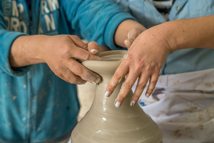 Midsection Of People Making Clay Pot