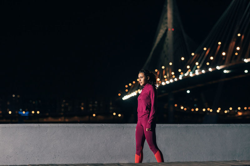 Woman standing on bridge at night