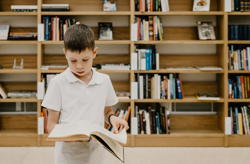 A boy stands in the library and reads a book while standing. preparing for homework.