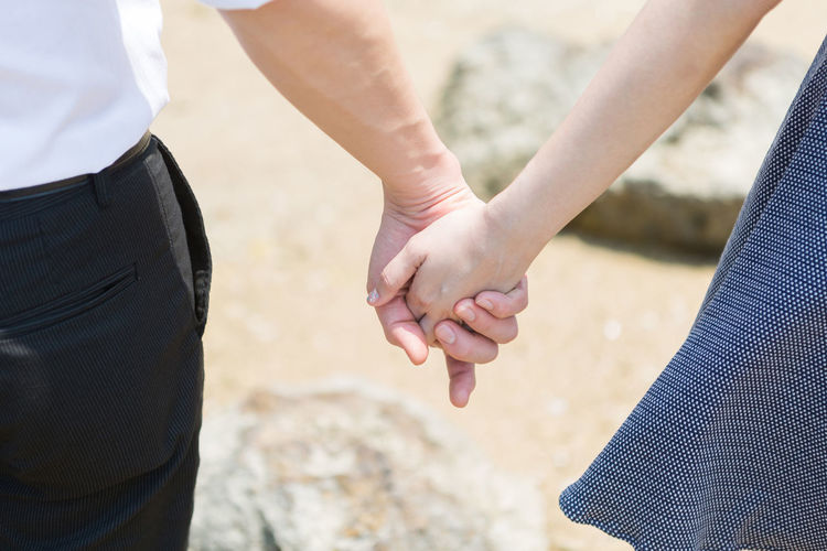Young couple touch hand together on the beach