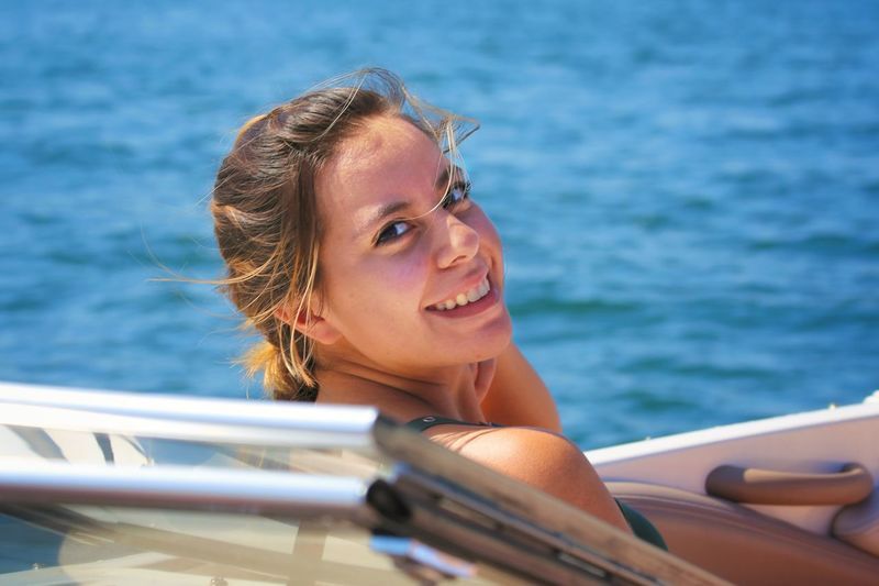 Portrait of smiling young woman in boat at sea