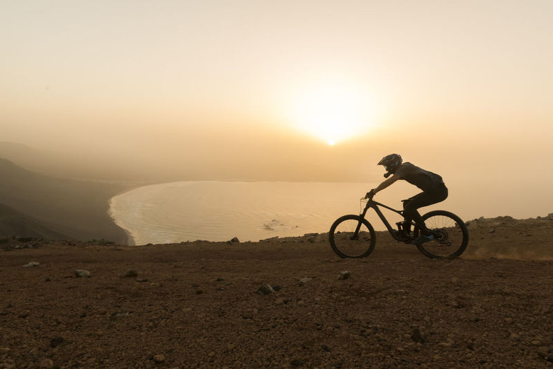 Silhouette person riding bicycle on road against sky during sunset