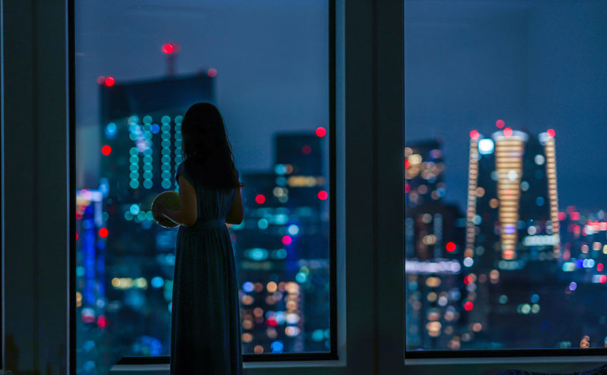 Rear view of woman standing by window at night