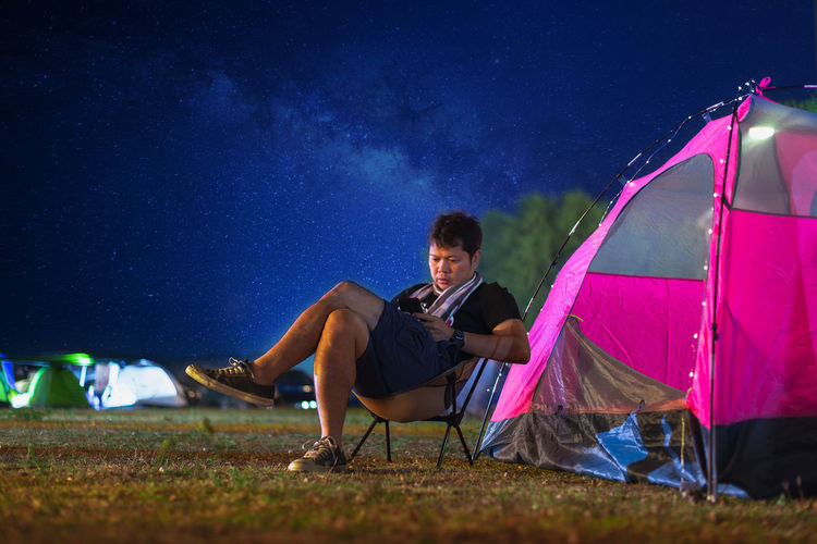 Man using phone while sitting on chair by tent on field at night