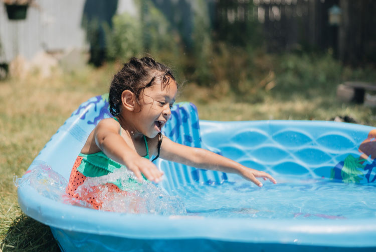 Mixed race young girl at home having fun on hot summer day in kiddie pool