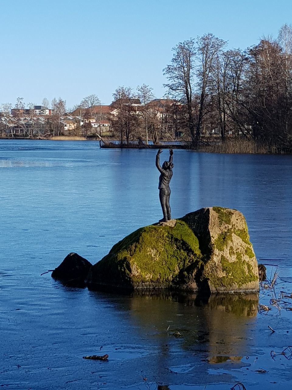 WOMAN STANDING ON ROCK BY LAKE AGAINST SKY