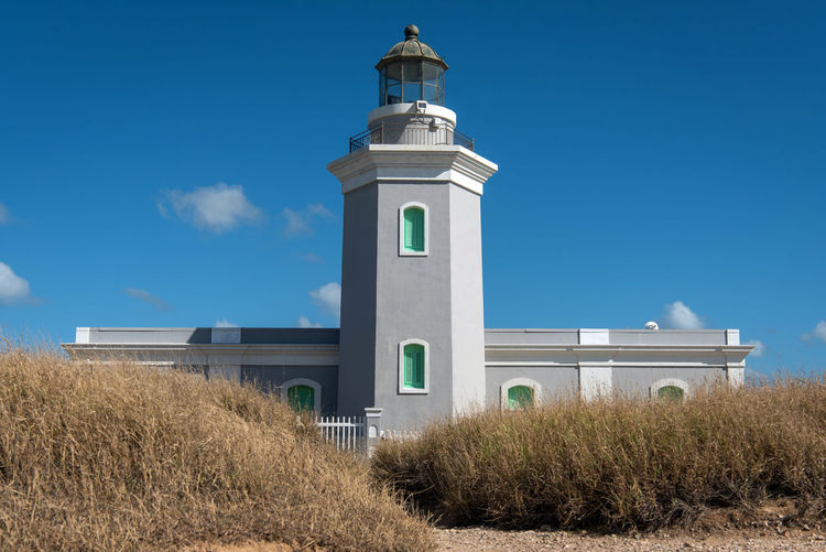 Low angle view of lighthouse on field against sky