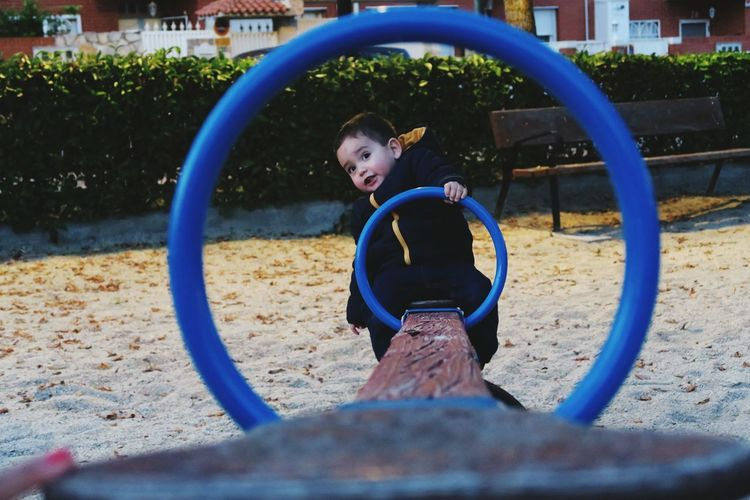 Cute boy sitting on seesaw at playground in park