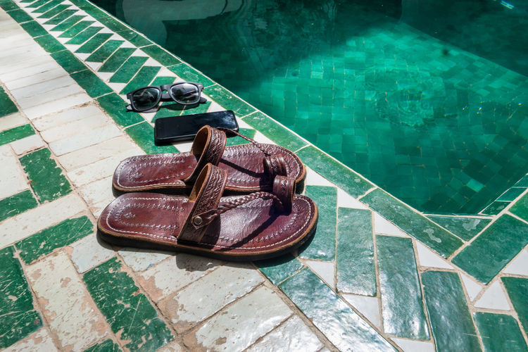 Morocco Travel Sandals Marrakesh Riad Destination Lifestyle Sandal Summertime Vacations Absence Architecture Close-up Day Flooring Green Color High Angle View Indoors  Nature No People Old Pool Poolside Reflection Shoe Summer Swimming Pool Turquoise Colored Water Wood - Material