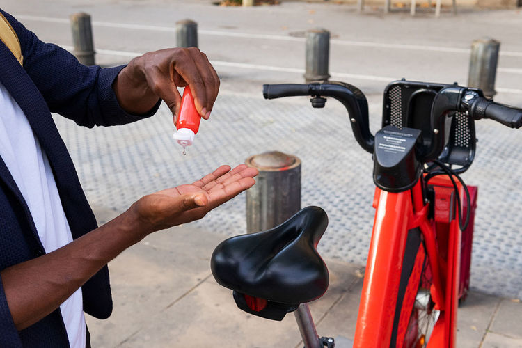 Midsection of man holding bicycle in city