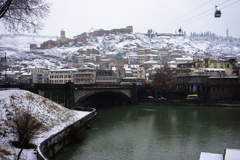 Architecture Bridge Building Exterior Built Structure Canal City Life Community Connection Day Development Famous Place Human Settlement Outdoors Residential District Residential Structure River Snow Tbilisi Tbilisi, Transportation Travel Water Waterfront