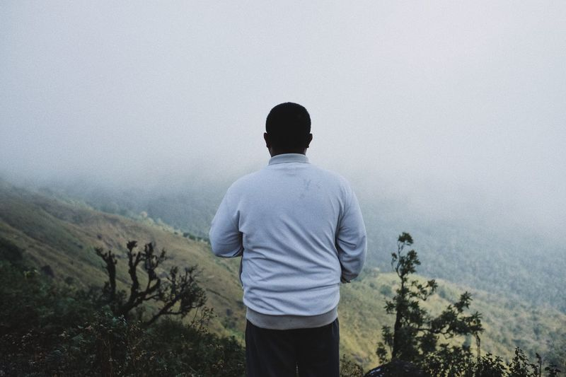 Rear view of man standing against mountain during foggy weather