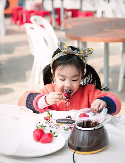 Girl Eating Chocolate Covered Strawberry At Table