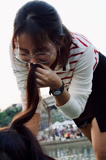 Young woman smelling hair of friend against sky