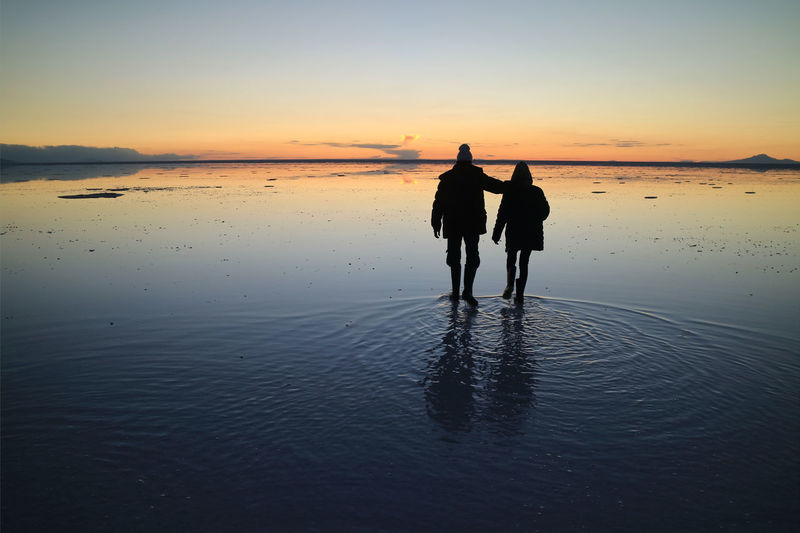 Silhouette couple on beach against sky during sunset