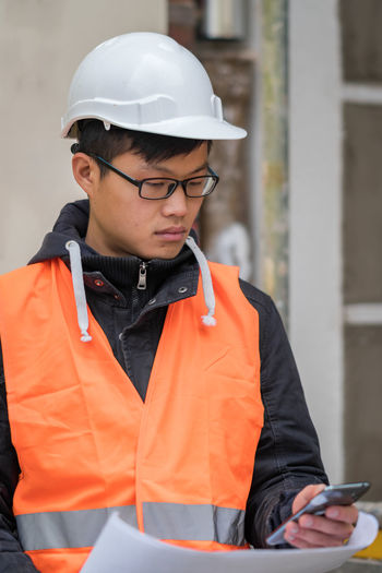 Young Asian engineer wearing protective work wear working on construction site. Outdoors Architecture Asian  Construction Site Growth Improvement Man Plant Safety Hard Hat Work Asian Man Development Engineer Engineering Eyeglasses  Future Headwear One Person Outdoors Person Protective Workwear Real Estate Safety Helmet Safety Jacket Wireless Technology Working