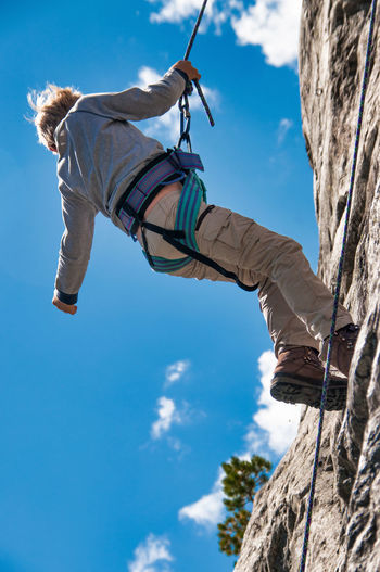 Low angle view of girl climbing on rock against sky