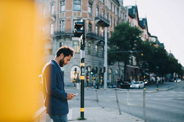 Side view of man looking at city street