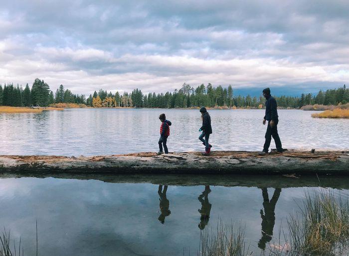 People on lake against sky