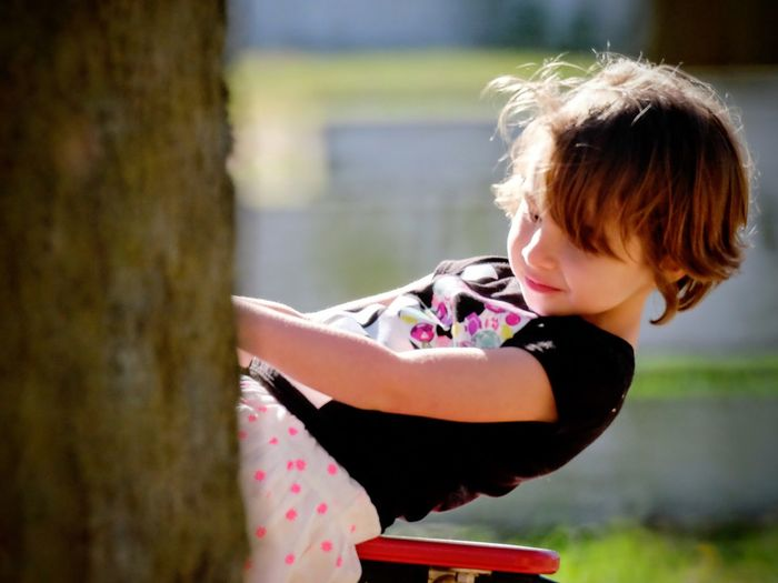 Side view of girl swinging on swing at park