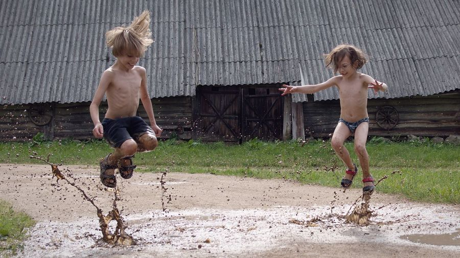 Full length of boys jumping in muddy water