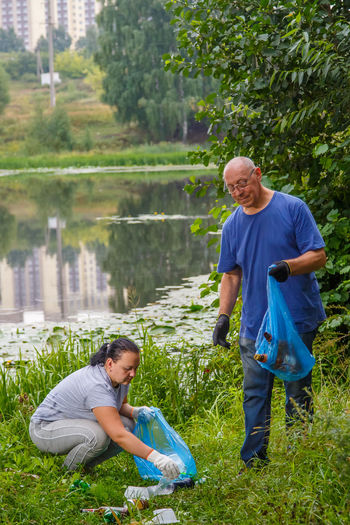 A man and a woman clean up a garbage dump in the nature. vertical photo