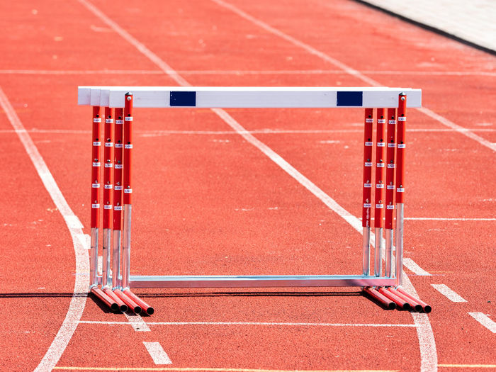 Hurdles and red running tracks in a stadion. beginning of athletic training