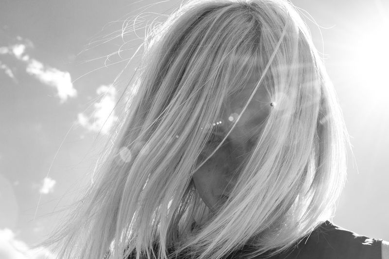 Portrait Of Woman With Tousled Hair Against Sky During Sunny Day