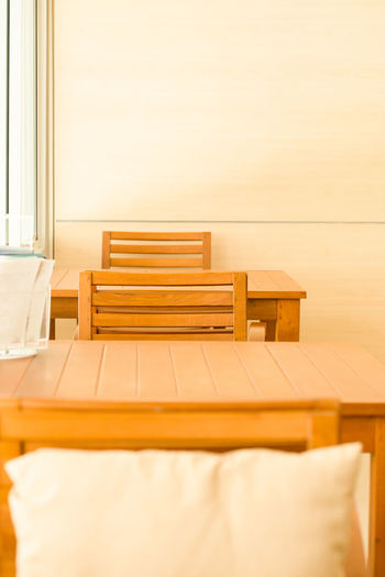 Empty chairs and table on bed against wall at home