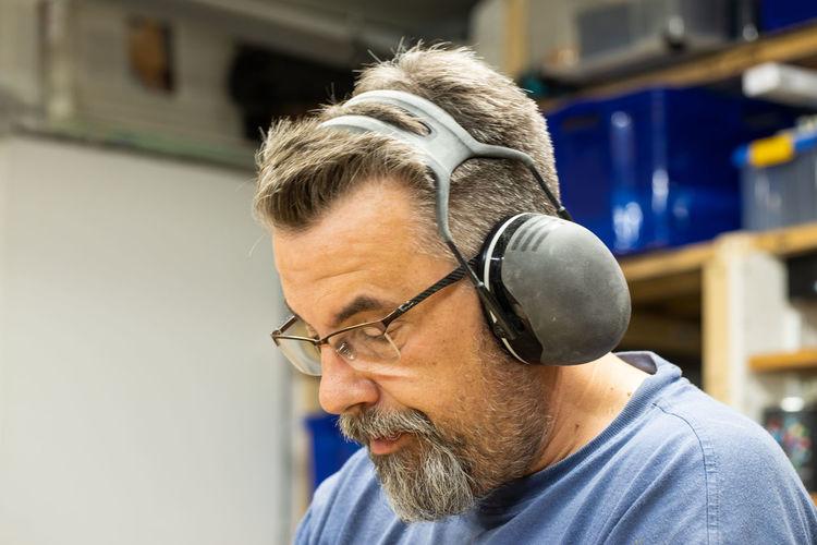 Manual Worker Wearing Eyeglasses And Ear Protectors Working In Workshop