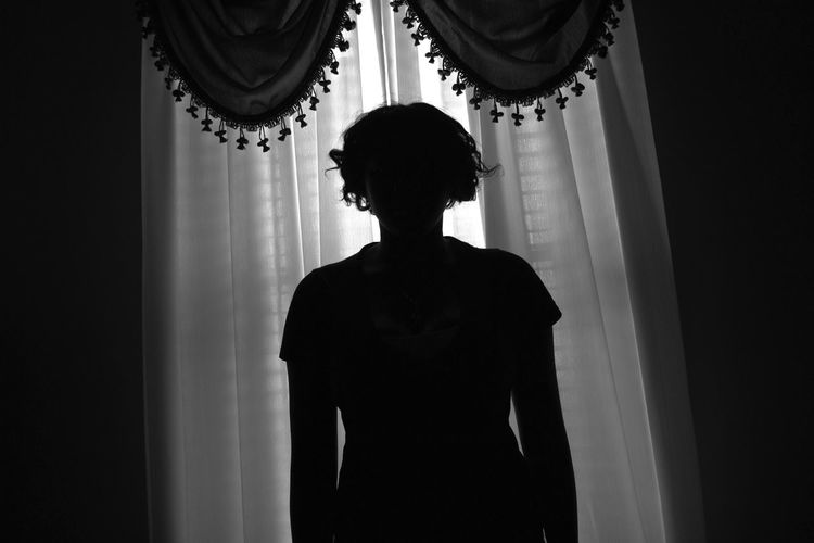 Rear view of silhouette woman standing against curtain