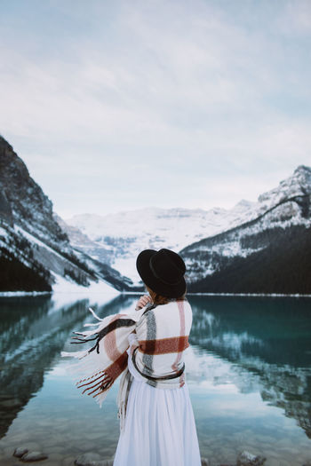 Rear view of woman standing in lake against mountains
