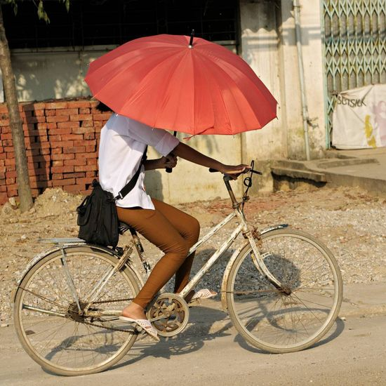 Man riding bicycle on wet street