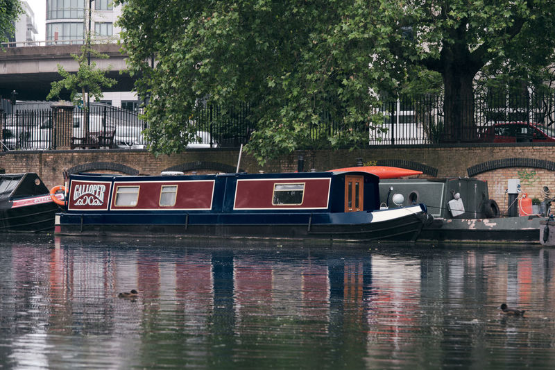 Boat moored in canal by trees in city